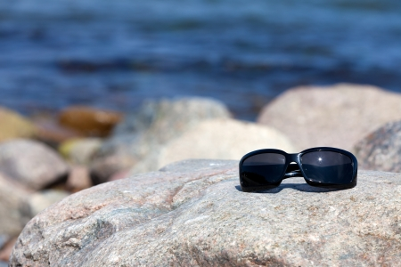 tinted glasses: Sunglasses with dark tinted glasses lies on a rock on the coast