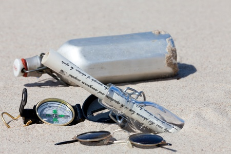 Treasure hunt on an island with compass and bottle message photo