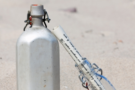 A canteen and message in a bottle are in the desert sand photo