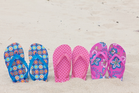 Three pairs bath slippers in a row stuck in the sand beach