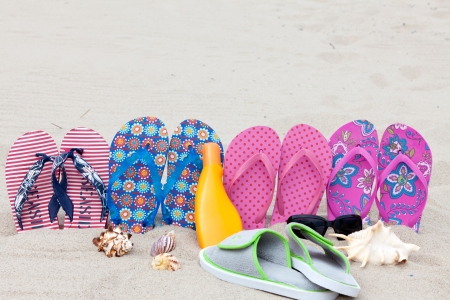 Four pairs bath slippers in a row stuck in the sand beach photo