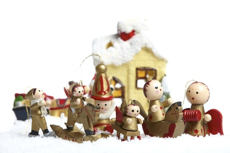 Small wooden Christmas tree decorations figures stand in the snow photo