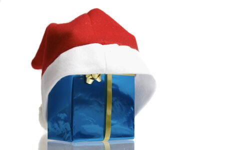 pulled over: Santa claus cap pulled over a blue christmas package