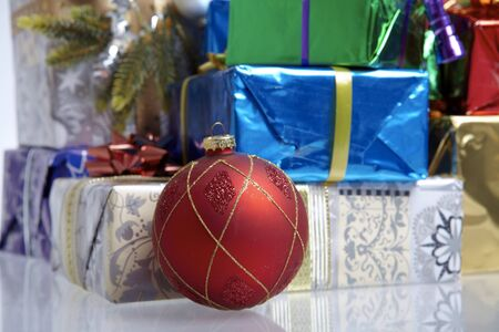 A red christmas tree ball in front of many christmas packages photo