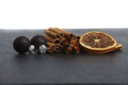 Cinnamon sticks, star anise and dried orange slices on a slate photo