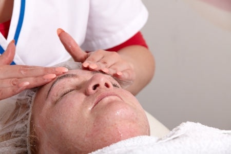Beautician treated in a beauty salon, a customer receives a facial scrub and a massage photo