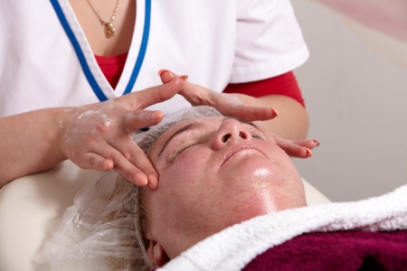 Beautician treated in a beauty salon, a customer receives a face mask and a massage photo