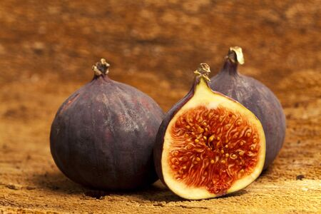 halved  half: Two whole and a halved fig on old tree bark as background