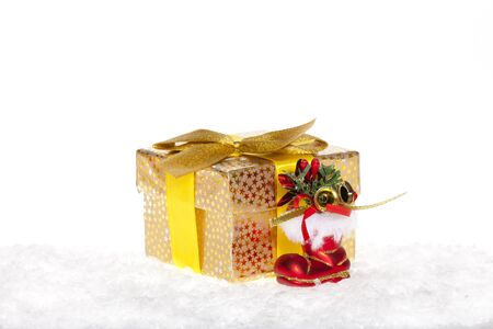 Golden Christmas gift with ribbon and red santa claus boots in the snow isolated on white photo