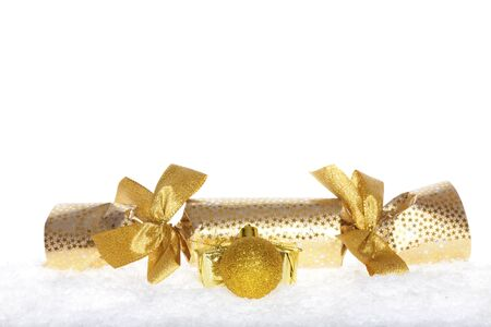 Christmas surprise wrapped in gold paper with ribbons and a golden christmas ball in the snow isolated on white photo