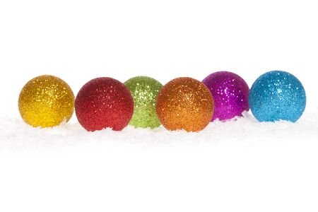 Some colorful Christmas baubles in the snow isolated on white photo