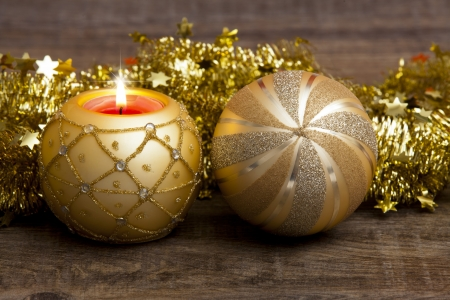 Candle in the golden candle holder and golden Christmas tree ball with golden garland on wooden background photo