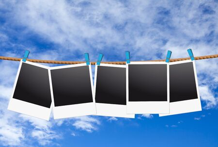 instant message: Five blank instant picture with clothespins fixed hanging on the clothesline front of blue sky