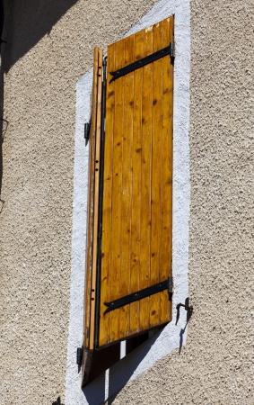Window with shutters on a medieval house in Gruissan, Southern France photo