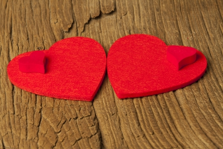 Two large and two small hearts of felt on old brown wooden board Stock Photo - 17317506
