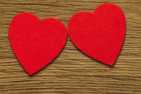 Two large red hearts of felt on old brown wooden board Stock Photo - 17317513