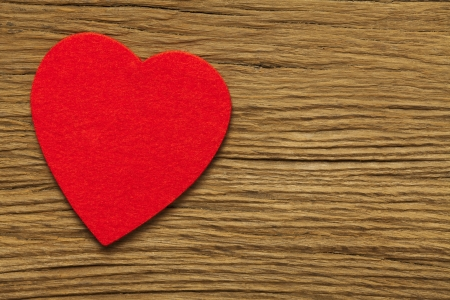 One large red hearts of felt on old brown wooden board Stock Photo - 17317512