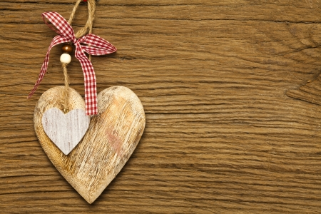 One large and a small wooden heart on a old brown wooden board Stock Photo - 17317510
