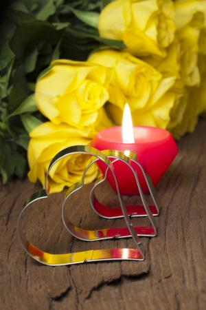 Bouquet of yellow roses, a tea light and three metal heart shape on old wooden board photo