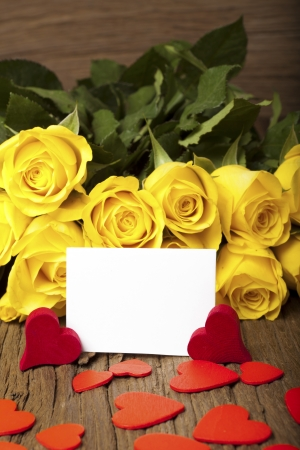 Bouquet of yellow roses and many red hearts with a writable white card on a old wooden board Stock Photo - 17317479
