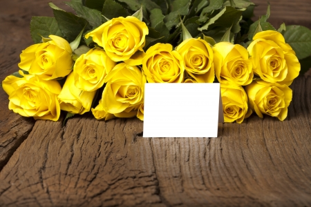 Bouquet of yellow roses with a writable white card on a old wooden board Stock Photo - 17317494