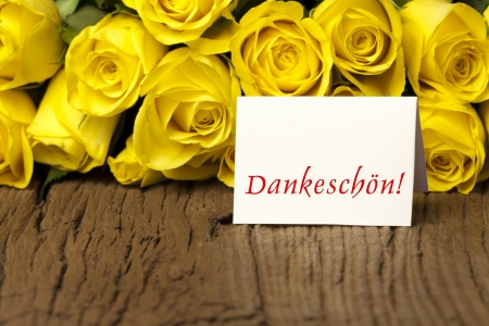 Yellow roses on old wooden board and a card with the german word  Dankesch&Atilde,&para,n  photo