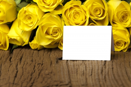 Bouquet of yellow roses with a writable white card on a old wooden board Stock Photo - 17317476