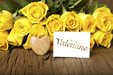 Yellow roses with a heart of stone and a card with the words  Be my Valentine  photo