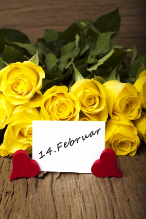 Yellow roses with two red wooden haerts and a card with the words  14  February photo