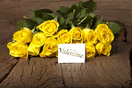 Yellow roses on old wooden board and a card with the words  Be my Valentine  photo
