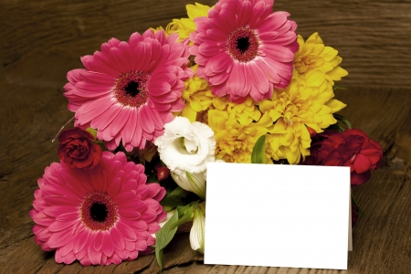 writable: White writable card in front of a bunch of colorful flowers on a massive old wooden background