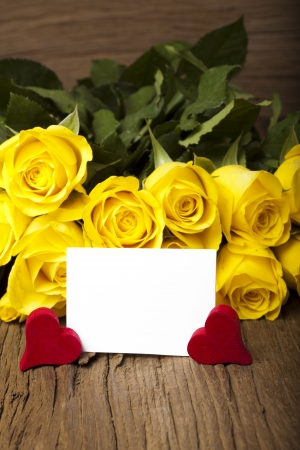 writable: Bouquet of yellow roses with a writable white card on a old wooden board Stock Photo