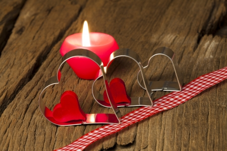 Three metal heart shapes and a candle with a red and white checkered deco ribbon on a old wooden board