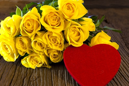 Red heart made of felt in front of a bunch of yellow roses on a massive old wooden background Stock Photo - 17625888