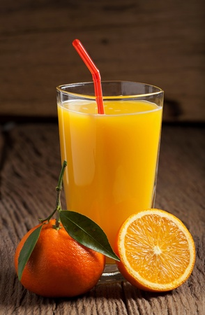 Freshly squeezed orange juice with a drinking straw on an old wooden table