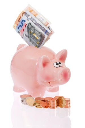 Pink piggy bank with stacks of euro coins and bills in front of white background photo