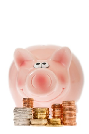 Pink piggy bank with stacks of euro coins against white background photo