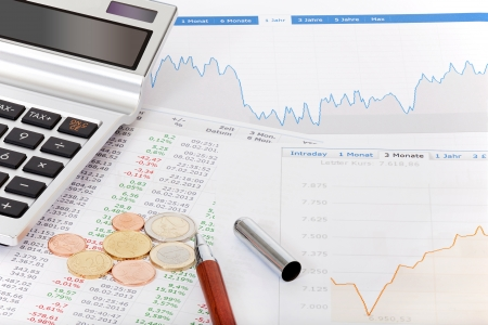 Stock quotes, charts, tables, calculator and money on a desk