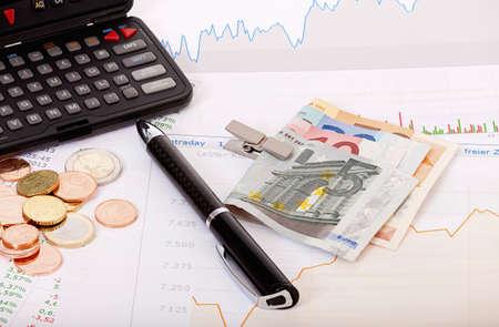 retained: Cotizaciones de las acciones, gr�ficos, tablas, calculadora y dinero en un escritorio