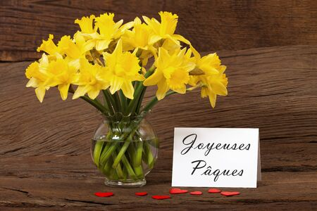 Easter greeting with a bouquet of daffodils and a white card with the text  Joyeuses Paques  Stock Photo - 17911414