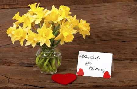 Dear greetings for Mothers Day with a bouquet of daffodils and a white card with the text  Alles Liebe zum Muttertag Stock Photo - 17911409