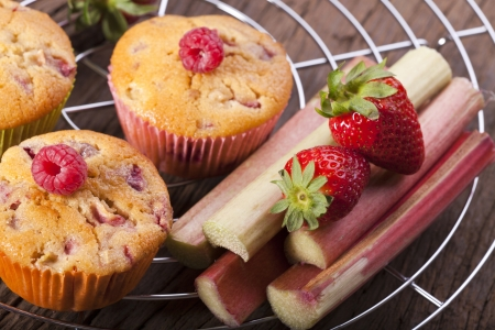 Two whole muffins and fresh strawberry and rhubarb on a cake wire rack