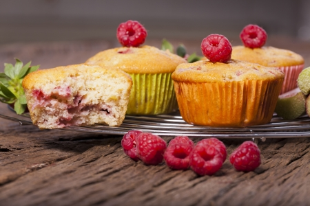 Some whole muffins and one bitten muffin on a cake wire rack with fresh raspberries on the front side photo