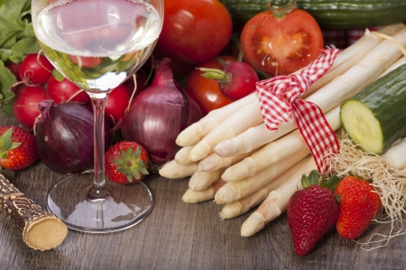 Fresh vegetables and seasonal ingredients with asparagus, onions, tomatoes a glass of white wine on a wooden background
