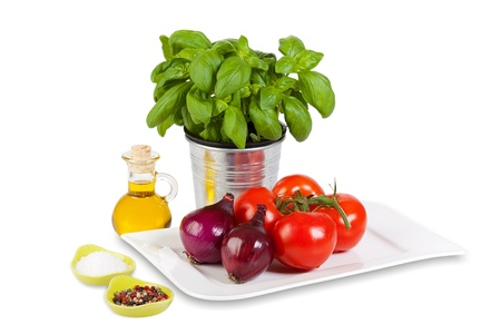 Ingredients for a tomato salad with basil isolated on white background photo