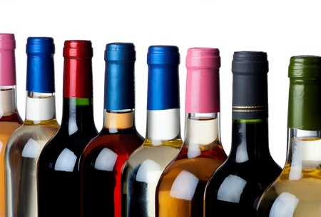 Different closed wine bottles in a row against white background photo
