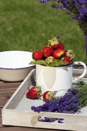 Fresh strawberries and freshly cut lavender lying on a wooden tray photo
