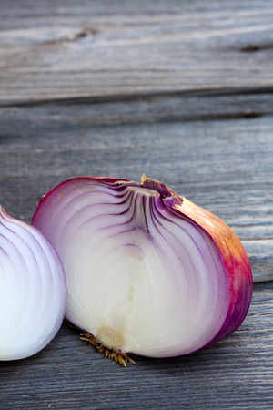 Close up view of a whole and a halved fresh red onion on a old wooden Table photo