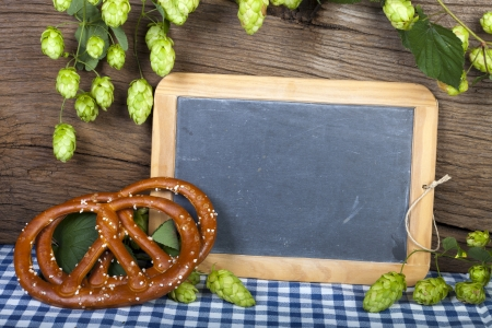 writable: Blank writable slate blackboard with hops and two pretzels in front of a rustic brown wooden wall