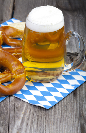 A cold beer in a beer glass with engraving and pretzels on napkins with blue and white rhombuses on a rustic wooden table photo